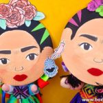 Two Frida Kahlo crafts for kids made with paper plates posing as if they were taking a selfie.